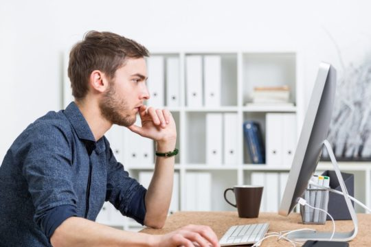Man-Uses-Computer-Mouse-In-Office-With-Side-Profile.jpg