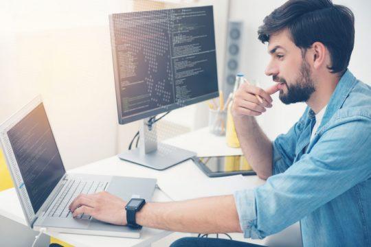 Computer-Programmer-Examining-Development-Code-On-Laptop-And-Computer-Screen.jpg