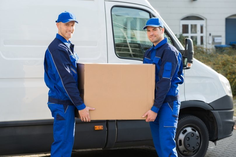 Movers-Carrying-Cardboard-Box-Beside-Truck.jpg