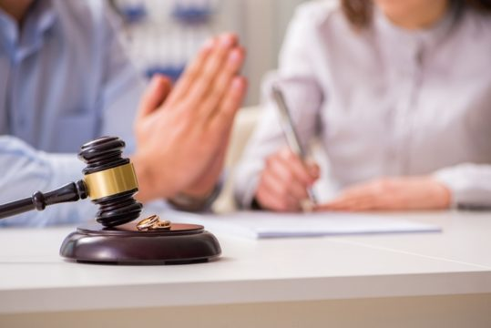 Divorce-Papers-Signed-By-Wife-With-Pleading-Husband-And-Legal-Gavel.jpg