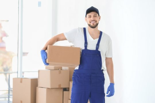 Mover-Carrying-Box-With-More-Cardboard-Boxes-Behind-Him.jpg