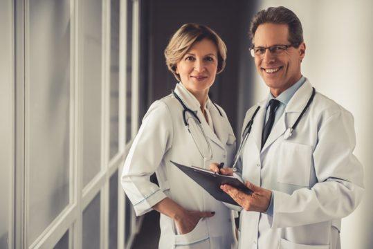 Senior-Doctors-In-Lab-Coats-With-Clipboard-Standing-In-White-Corridor.jpg