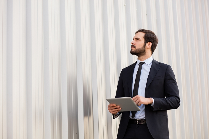 Business-Man-With-Tablet-Inspects-Steel-Building-Wall.jpg